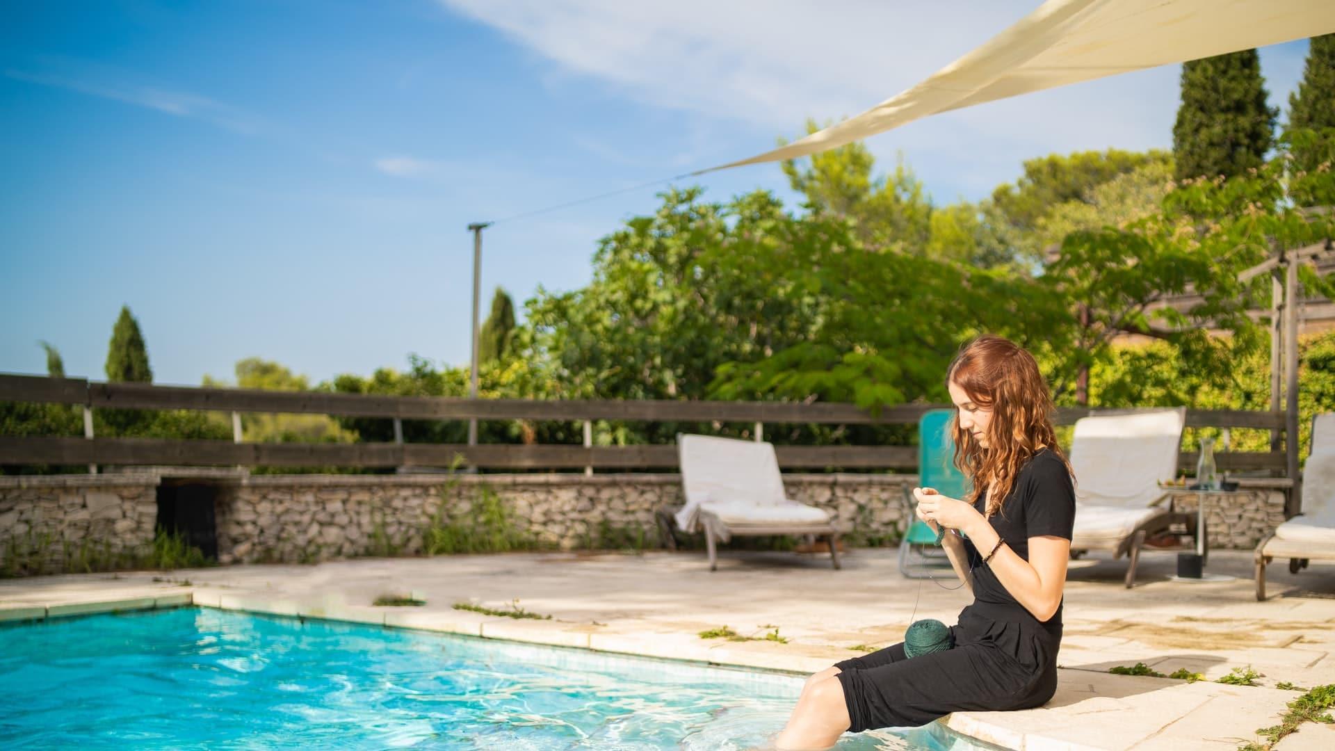 jeune femme assise sur la margelle d'une piscine